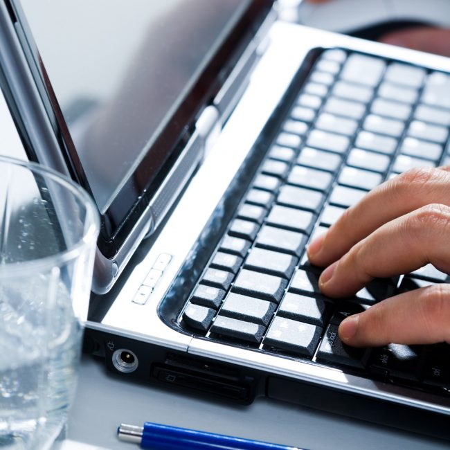 Image of human hands pressing the buttons of keyboard with pen and glass near by