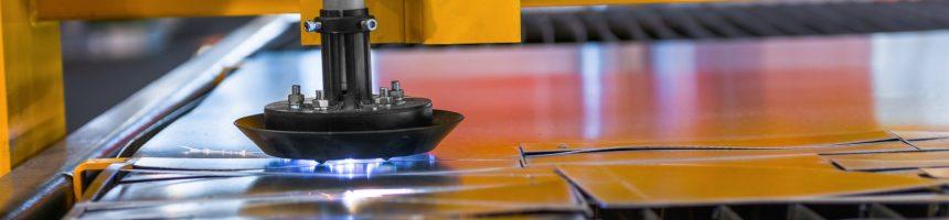 Machine cutting steel in a factory closeup